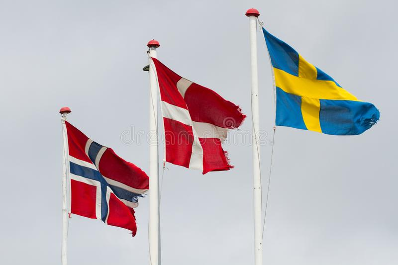 Three scandidavian flags in the wind against the sky stock photo