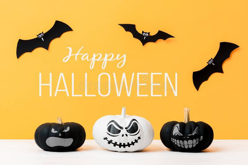 Three scary Black and White Jack o Lanterns and flying paper bats over yellow background. Halloween background. Three scary Black and White Jack o Lanterns and stock image