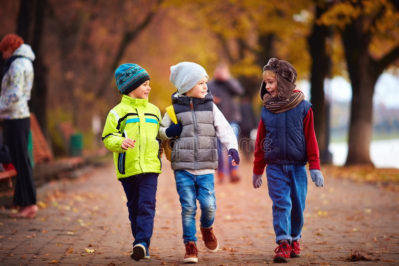 Three school friends, kids walking on the autumn street stock image