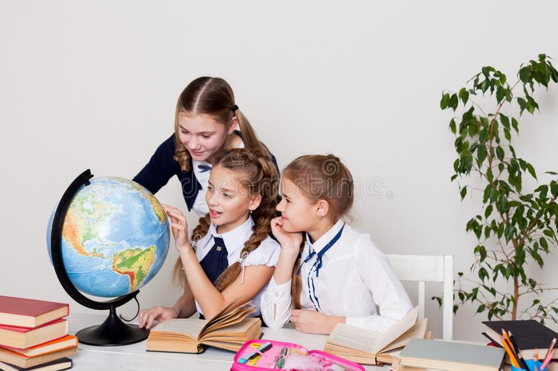 Three schoolgirls girls learn world geography lesson on the map stock photography