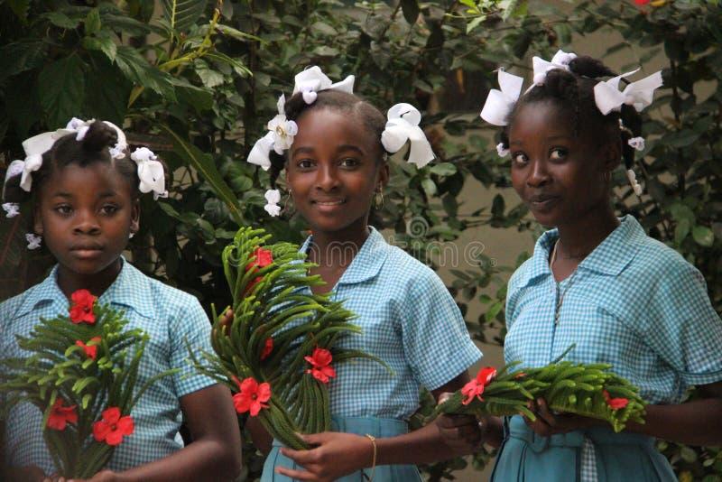 Three schoolgirls hold welcoming wreaths for missionaries in rural Robillard, Haiti. Three beautiful schoolgirls hold homemade gifts for missionaries to rural stock photo