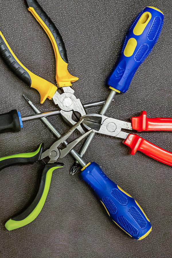 Three screwdrivers blue rubber set pliers red yellow green macro hand tools background repair stock photos