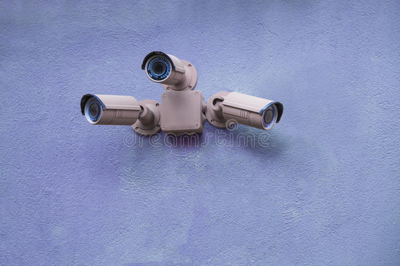 Three security cameras. On blue wall stock photography