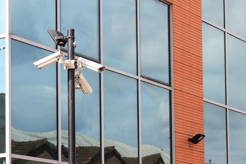 Download Three Security Cameras On Front Of Glass Building Stock Image - Image: 26425301
