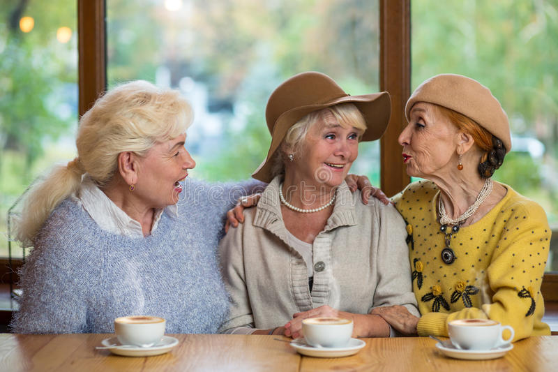 Three senior ladies in cafe. Women talking to each other. The best friends royalty free stock image