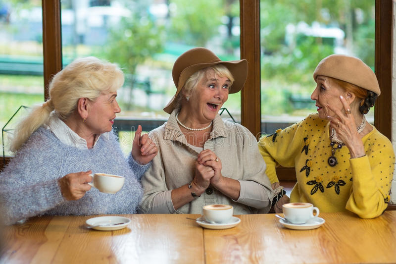 Three senior ladies drinking coffee. Surprised women at the table. Share happiness with best friends royalty free stock photo