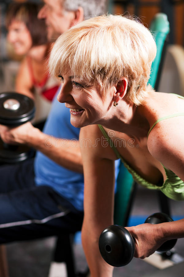 Three senior people in gym. Three senior people in the gym lifting dumbbells, exercising stock photography
