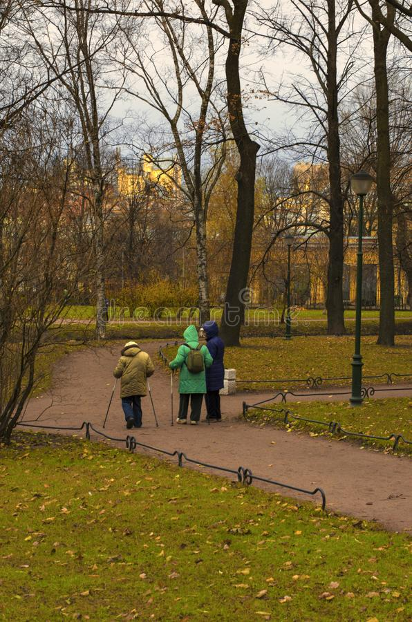 Three seniors engaged in Nordic walking in the Park. Saint Petersburg, Russia - November 16, 2018: Three seniors engaged in Nordic walking in the Park on a royalty free stock image