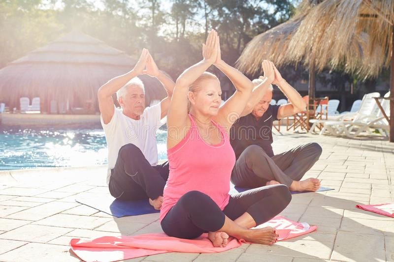 Three seniors at the spa hotel by the pool doing yoga exercise. With clasped hands stock photo
