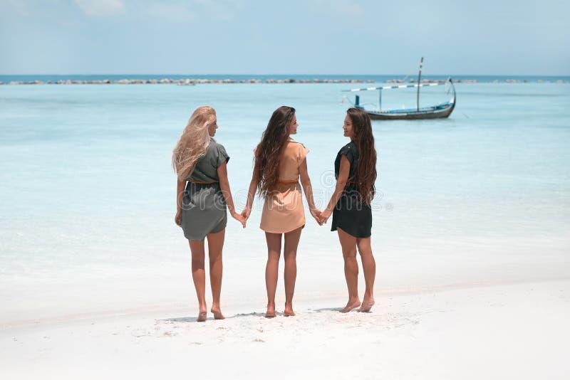 Three sexy Girls having fun on the beach. Women wearing alike dress posing on the sea shore. Slim cute models with healthy long stock photos