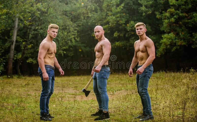 Three sexy guys. brutal guys pose with naked torso. handsome guys with sexy body. Sports and leisure. mesomorph. three. Muscular men with axe. athletic men use stock photo