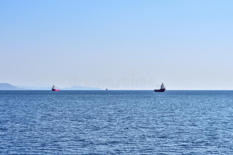 Three ships intended for the transport of containers at anchorage in the sea. Against the background of the mountainous coast and open sea stock photos