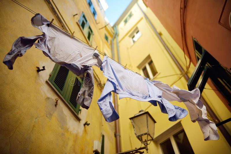 Three shirts drying on a rope in Riomaggiore, the largest of the five centuries-old villages of Cinque Terre, Italian Riviera,. Three shirts drying on a rope in stock photography