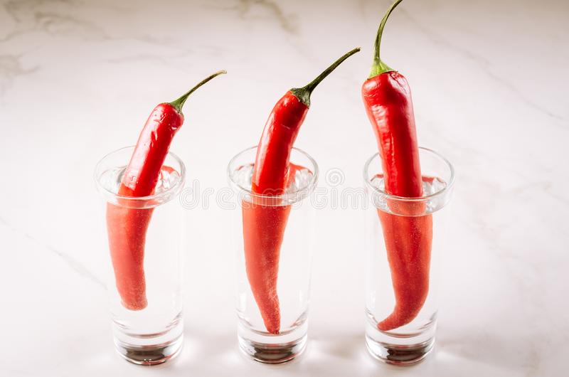 three shots of vodka and red pepper/three shots of vodka and red pepper on a white marble background. Selective focus royalty free stock photos