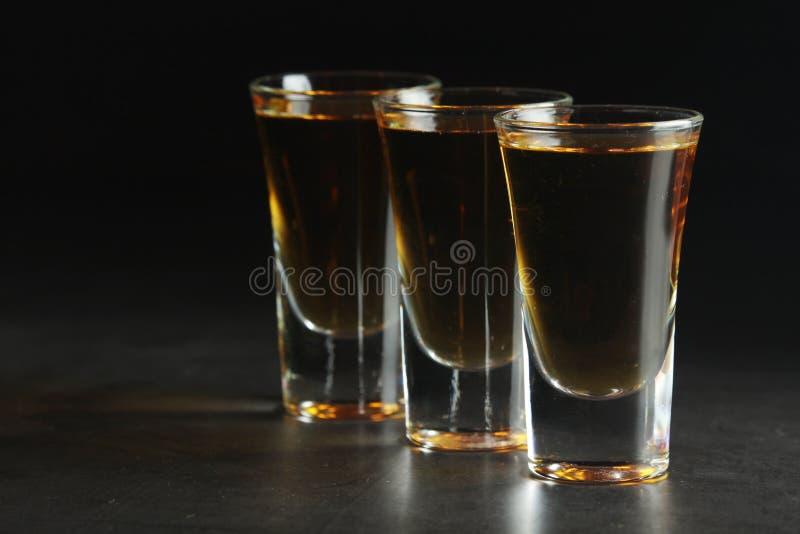 Three shots with whiskey at dark background royalty free stock photos