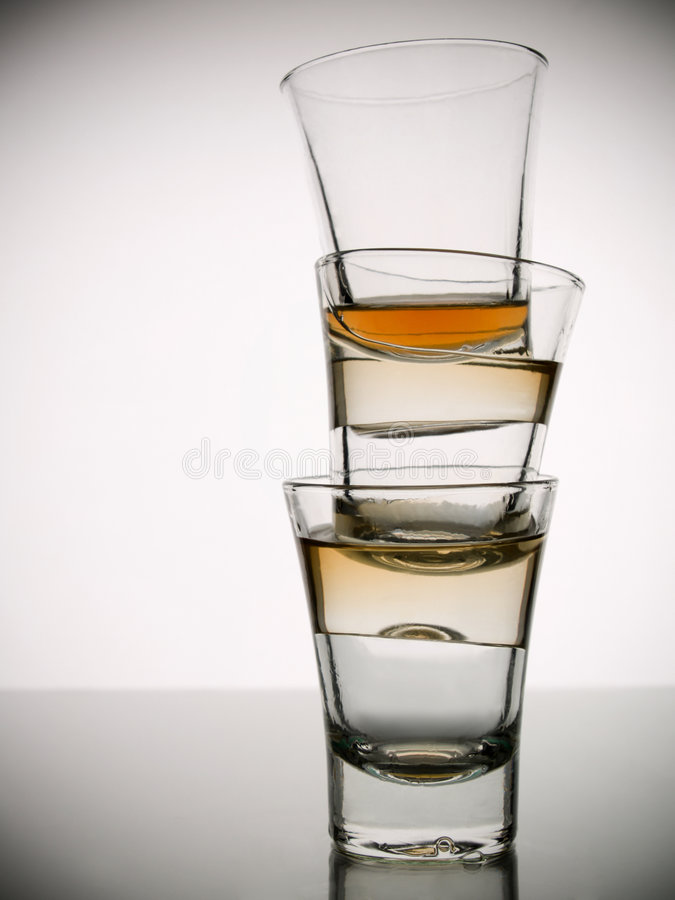 Three shots of whisky. A pile of three almost empty shots of whisky on white background over gray floor royalty free stock images