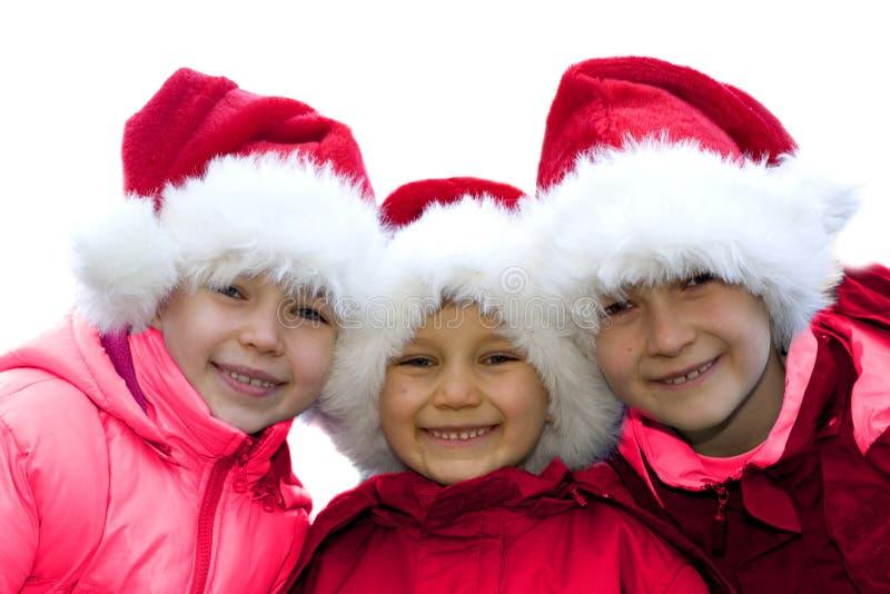 Three siblings dressed as Santas. royalty free stock images