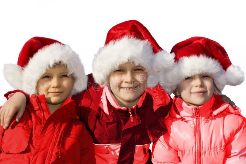 Three siblings dressed as Santas. stock photography