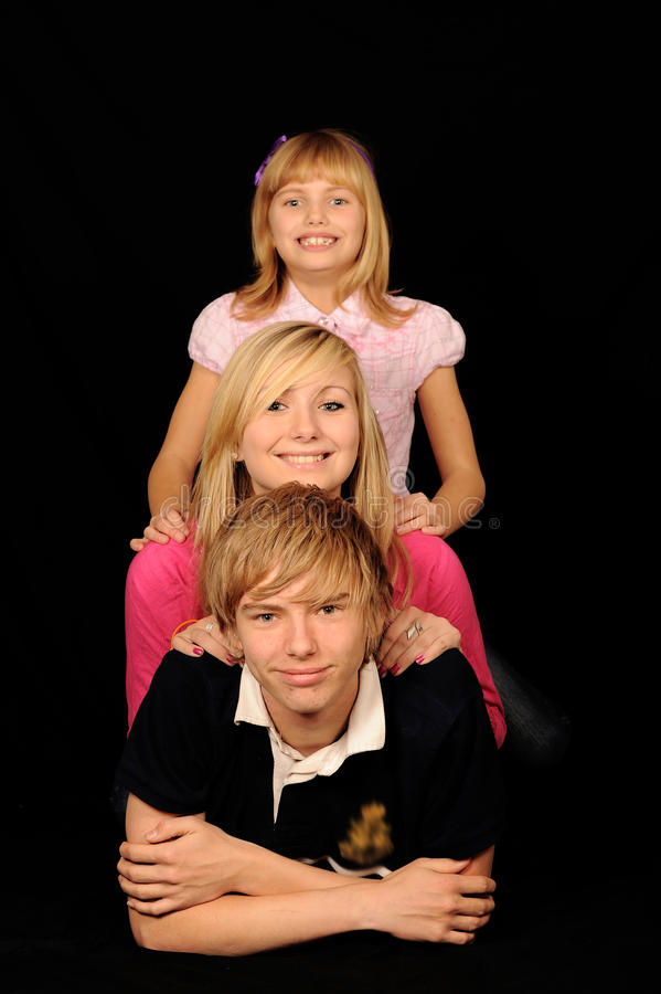 Three siblings posing. A studio portrait of three smiling siblings posing against a black background royalty free stock photo