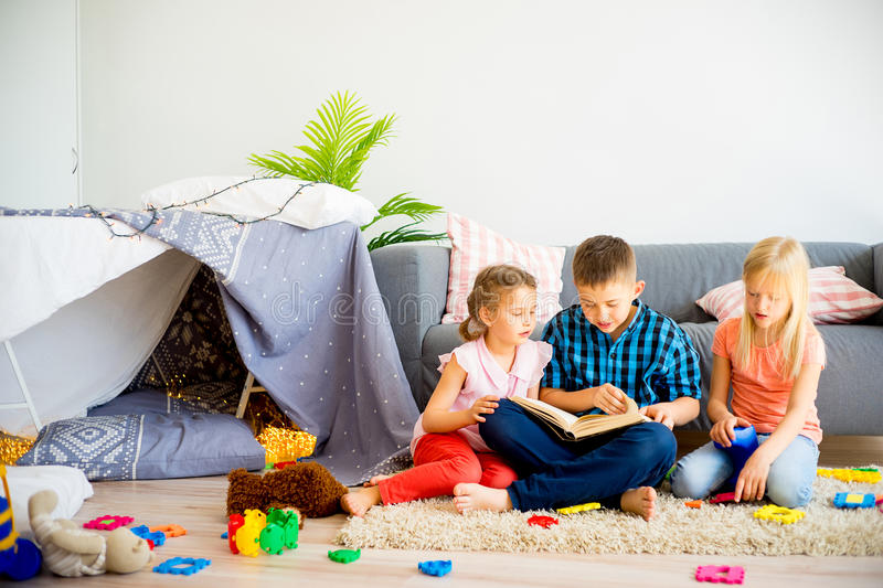 Three siblings reading a book stock images