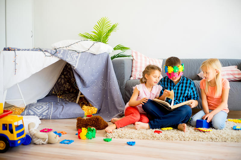 Three siblings reading a book stock image