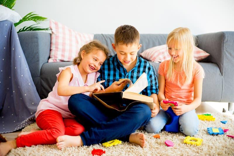 Three siblings reading a book royalty free stock photo