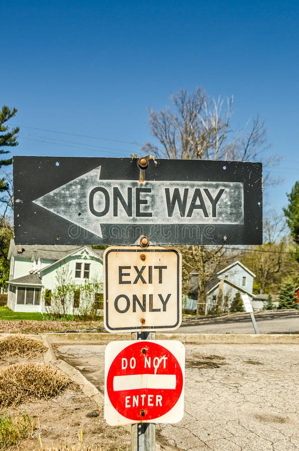 One Way, Exit Only, Do Not Enter Signs. Three signs showing years of weather and abuse causing rust and other damage royalty free stock image