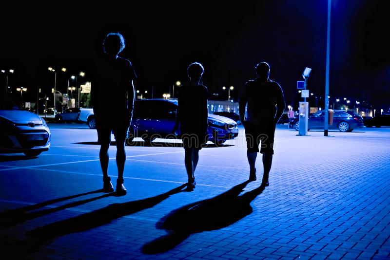 Three silhouettes walking in a parking lot with deep shadows royalty free stock photography