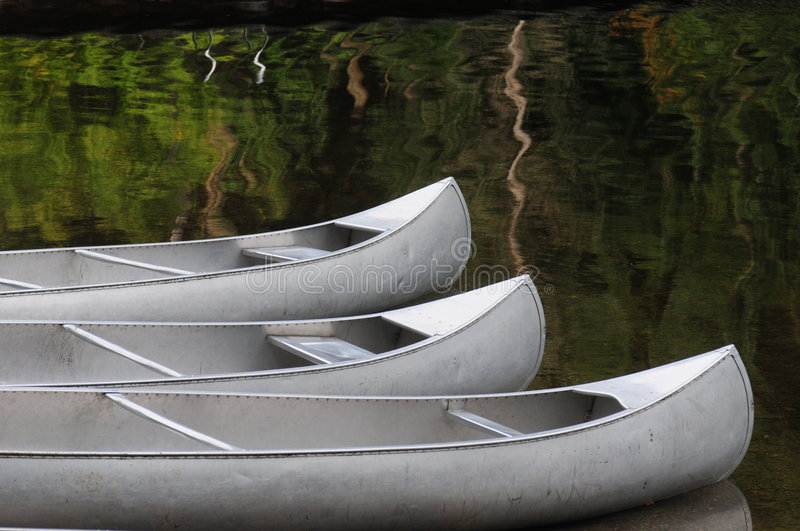 Three silver canoes on calm lake water royalty free stock photos