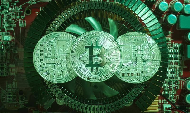 Three silver coins bitcoin are on the heatsink of the video card royalty free stock photos