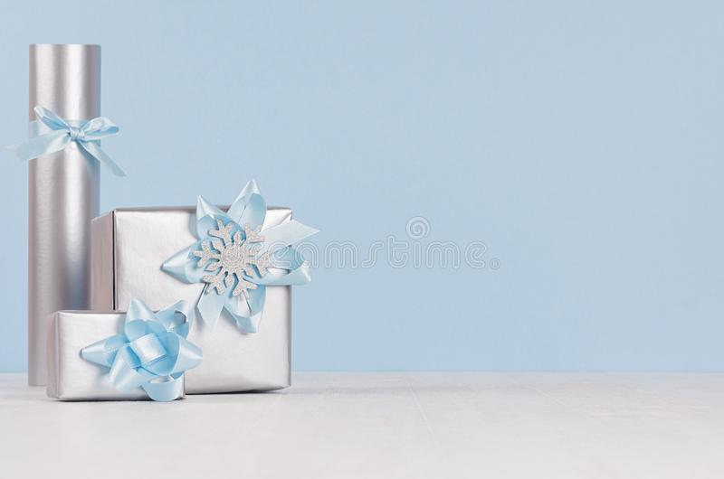Three silver metallic gift boxes with shiny ribbons and bows on soft light white wood board and pastel blue wall. stock images