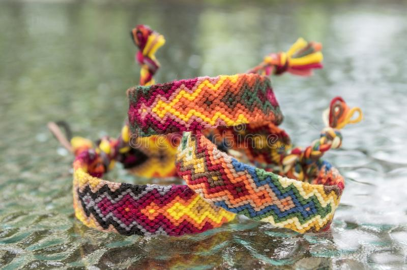 Three simple handmade homemade natural woven bracelets of friendship on glass table, rainbow colors, pattern. Three simple handmade homemade natural woven royalty free stock images