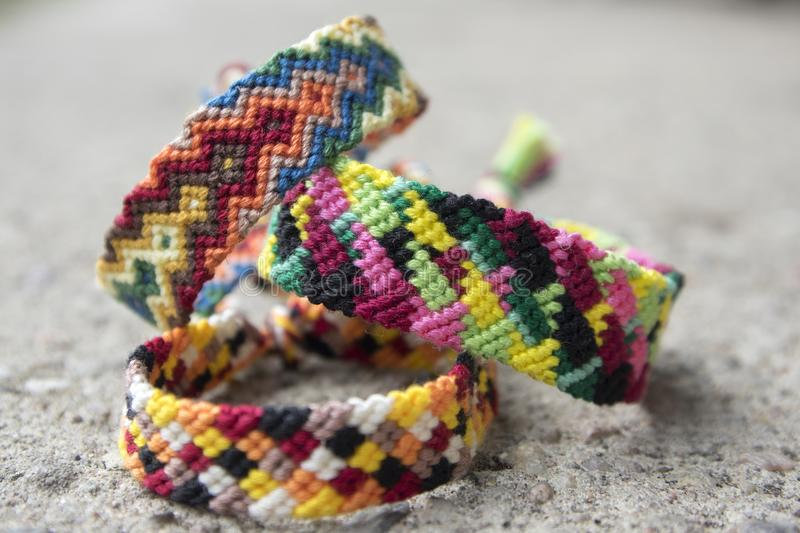 Three simple handmade homemade natural woven bracelets of friendship on grey concrete background, rainbow colors, pattern. Three simple handmade homemade natural stock photo