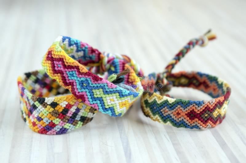 Three simple handmade homemade natural woven bracelets of friendship on light wooden background, rainbow colors. Checkered pattern stock photography