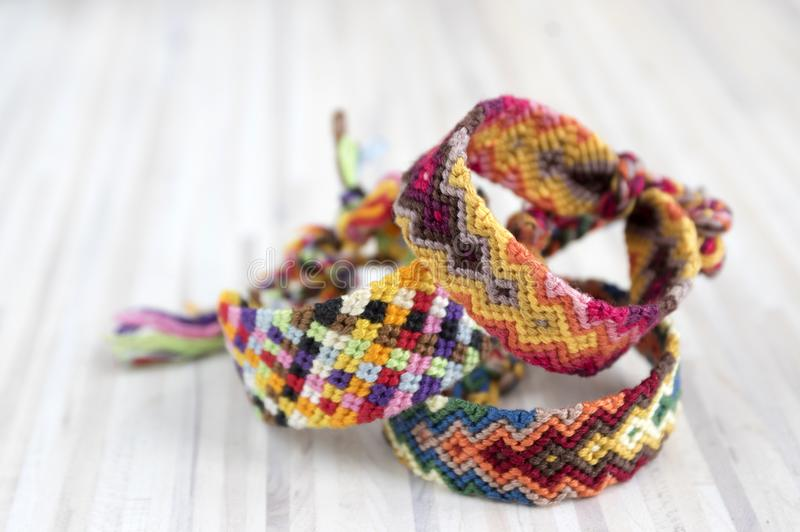 Three simple handmade homemade natural woven bracelets of friendship on light wooden background, rainbow colors, pattern. Three simple handmade homemade natural royalty free stock photo