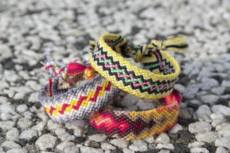 Three simple handmade homemade natural woven bracelets of friendship on stone background. Rainbow colors, checkered pattern royalty free stock photo