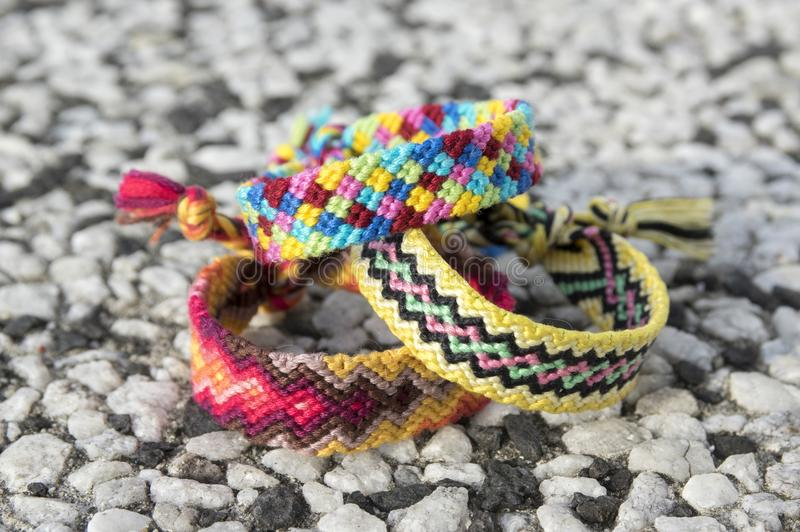 Three simple handmade homemade natural woven bracelets of friendship on stone background. Rainbow colors, checkered pattern stock image