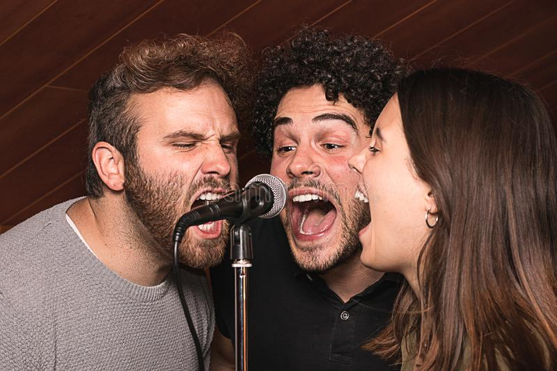 Three singers singing with a microphone with euphoric expression. Concept of music stock photography