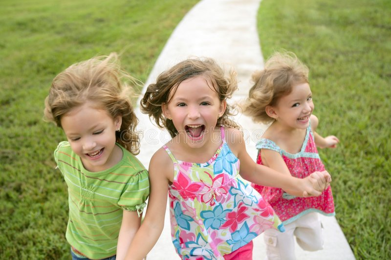 Three sister girls playing running on the park royalty free stock photography