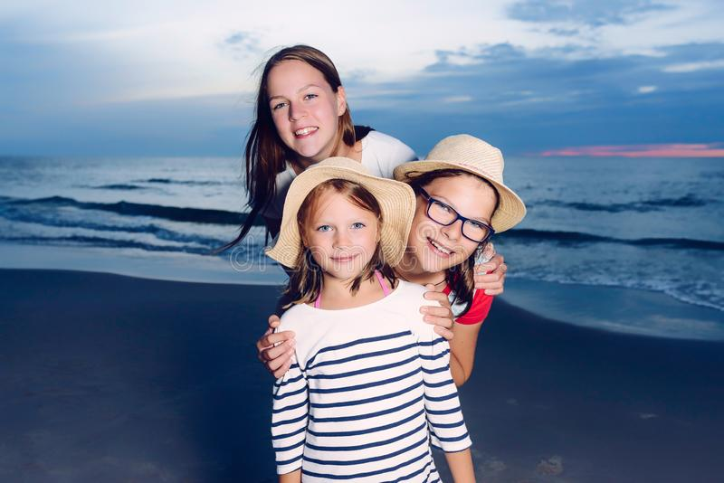 Three sisters having fun on beach, friends on beach in dusk time stock photo