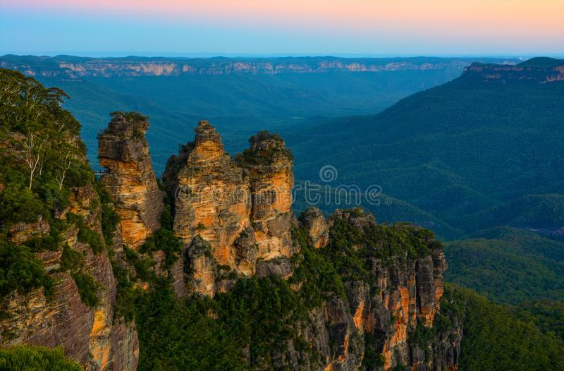 Three Sisters landmark in front of a backdrop of the Blue Mountains landscape just after sunset in NSW, Australia stock photography