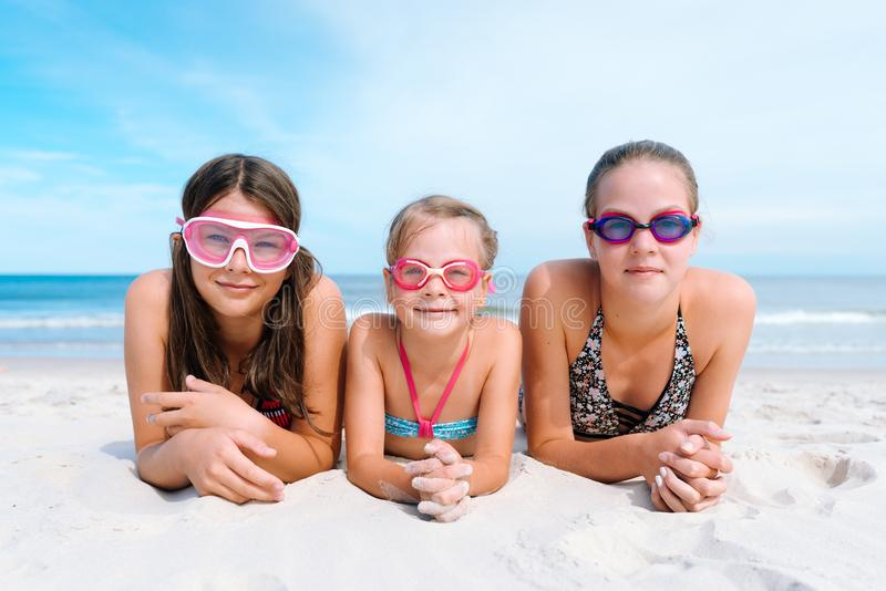 Three sisters on a seaside beach lying on their bellies in swimming goggles and swimwear royalty free stock photography