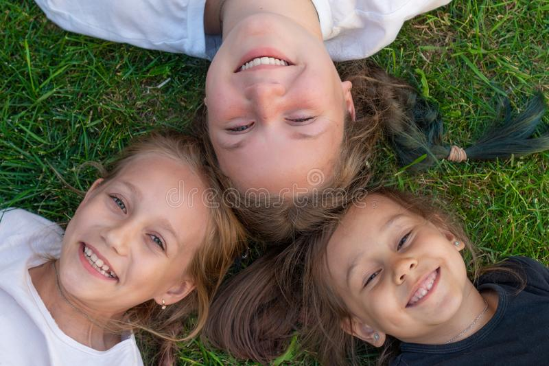 Three sisters summer portrait. Cute girls are lying on the grass and smiling. smiling children outdoor. Concept of summer stock photography