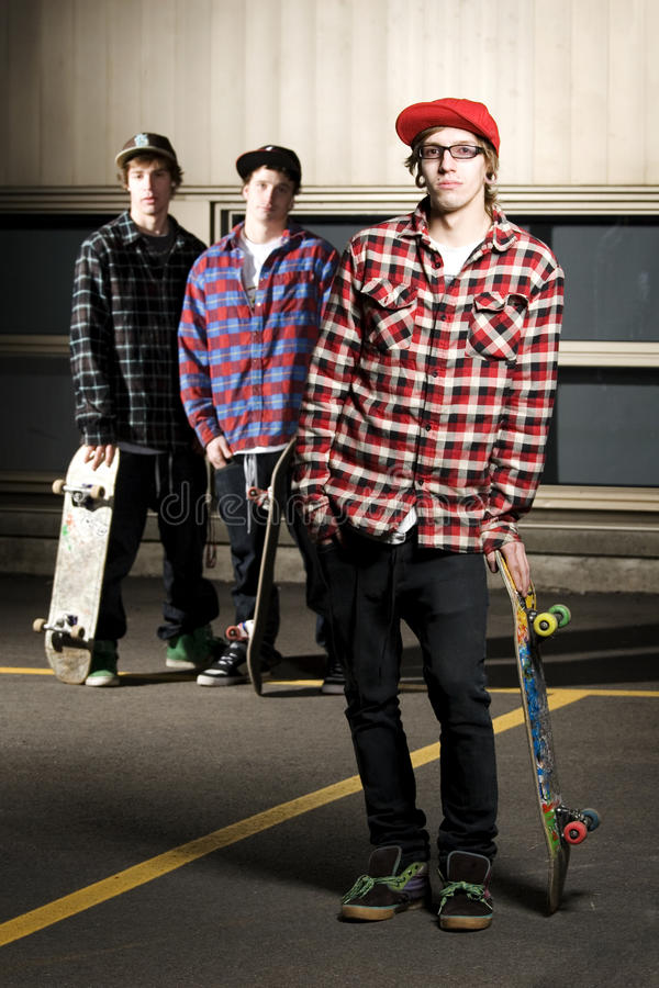 Three skateboarder kids standing in parking lot royalty free stock photo
