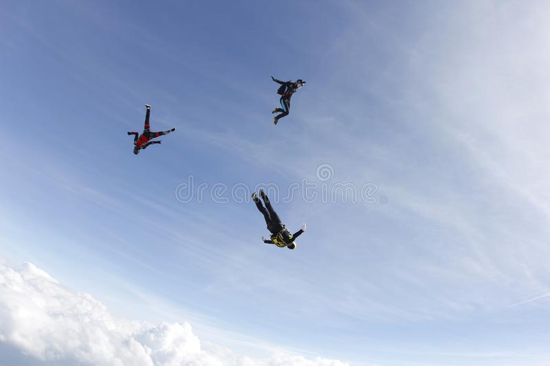 Three skydivers are in the blue sky. stock photography