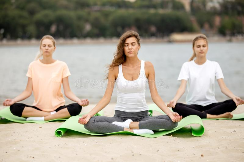 Three slender young girls sit in a yoga poses with closing eyes on mats on sandy beach next to the river on a warm day stock image