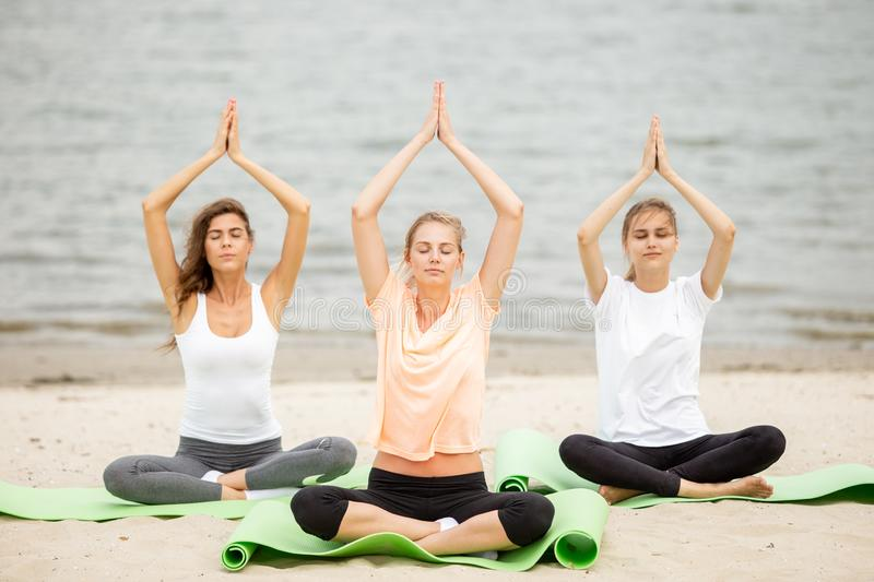 Three slender young girls sit in a yoga poses with closing eyes on mats on sandy beach on a warm day royalty free stock photo