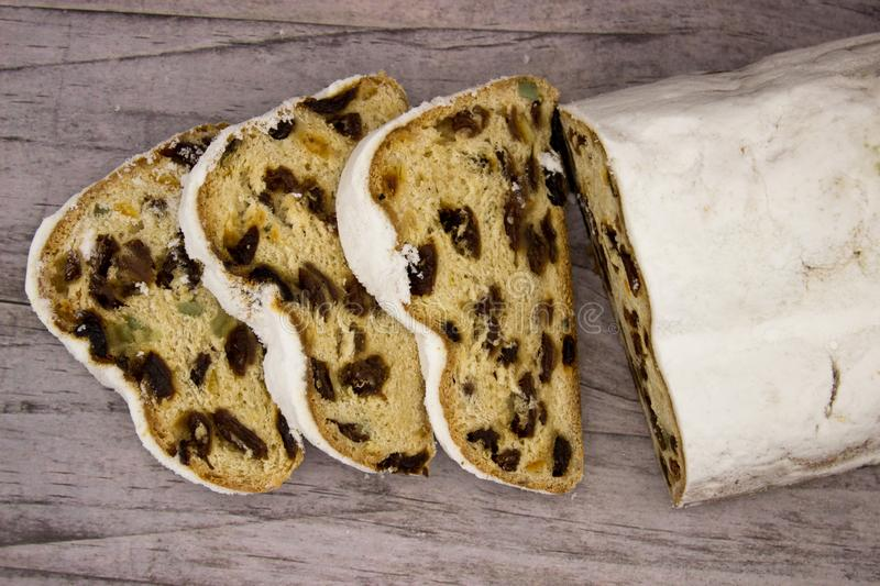 The three slices and the main part of Stollen on a wooden background. Traditional German Christmas cake with marzipan and dried stock image