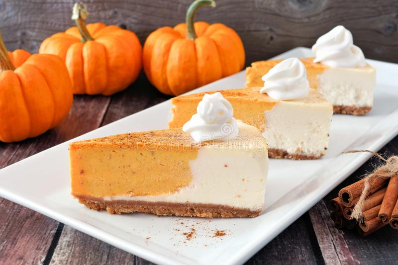 Three slices of pumpkin cheesecake on white serving plate royalty free stock image
