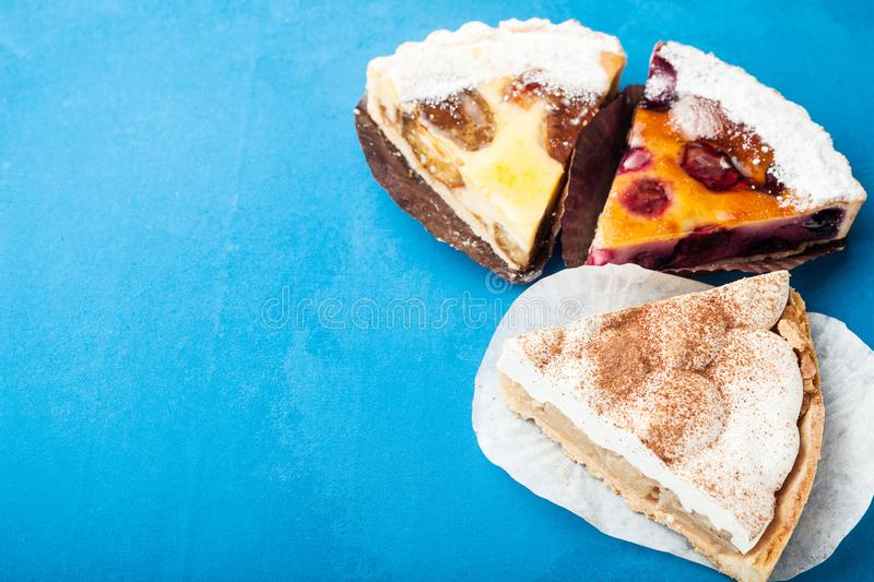 Three slices of sweet fruit pies on a blue background. Copy space stock images